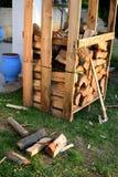 Pilas de madera en plataforma en hierba y el hacha imagenes de archivo