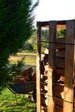 Pilas de madera en plataforma y carretilla en jardín fotografía de archivo