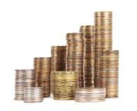 Pilas de monedas de plata y de oro aisladas Imágenes de archivo libres de regalías