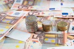 Pilas de monedas en billetes de banco Fotografía de archivo libre de regalías