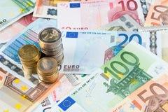 Pilas de monedas en billetes de banco Foto de archivo