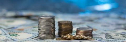Pilas de monedas en dispersado cientos billetes de dólar en un fondo azul con efecto del bokeh ilustración del vector