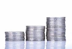 Pilas de monedas en el fondo blanco Fotos de archivo