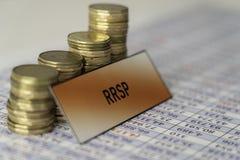 Pilas de monedas en la hoja de cálculo que muestra crecimiento en ahorros de RRSP foto de archivo