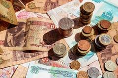 Pilas de monedas en las notas de papel Billetes de banco y monedas de los países diferentes imagenes de archivo