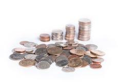 Pilas de monedas en un fondo blanco Fotos de archivo