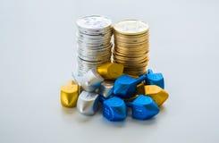 2 pilas de monedas de Jánuca rodeadas por los dreidels minúsculos Foto de archivo