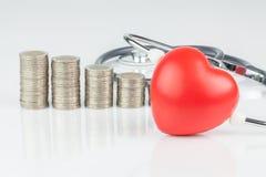 pilas de monedas y de corazón en el fondo blanco fotografía de archivo libre de regalías
