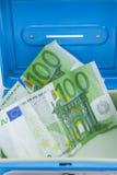 Pilas de monedas y de billetes de banco euro en una caja del efectivo Imagen de archivo libre de regalías