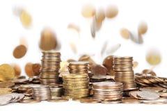 Pilas de monedas y de monedas que caen en fondo Imagen de archivo