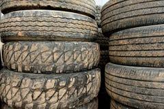 Pilas de neumáticos de goma negros gastados y fangosos usados imagen de archivo libre de regalías