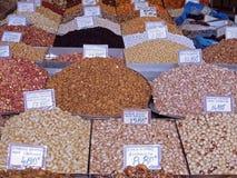 Pilas de nueces y de especias coloridas en un mercado de la comida imagen de archivo