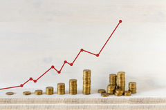 Pilas de oro de las monedas dispuestas como gráfico con la flecha roja en un fondo de madera Crecimiento del negocio y concepto d fotografía de archivo libre de regalías