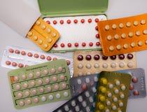 Pilas de píldoras anticonceptivas coloridas con el empaquetado moderno Foto de archivo