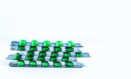 Pilas de píldoras azucaradas redondas verdes de la tableta en paquetes de ampolla en el fondo blanco con el espacio de la copia M foto de archivo