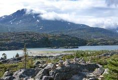 Pilas de piedras delante del lago del glaciar fotografía de archivo