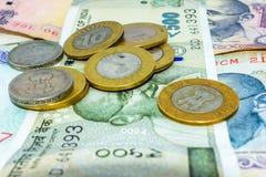 Pilas de rupias indias de la moneda en notas y de monedas en diversas denominaciones foto de archivo libre de regalías