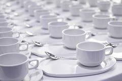 Pilas de tazas de café con las cucharillas de plata Fotos de archivo