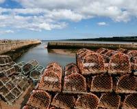 Pilas de trampas de la langosta en un embarcadero en Escocia Fotos de archivo libres de regalías