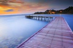 Pilastri di legno del ponte con nessuno e l'acqua di mare smoothy contro il damerino Fotografie Stock Libere da Diritti