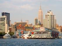 Pilastri e barche lungo Manhattan con l'Empire State Building Fotografie Stock Libere da Diritti