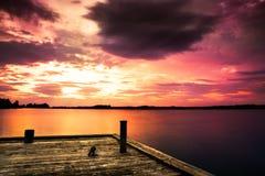 Pilastro al lago e ad un bello tramonto Fotografia Stock