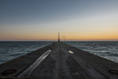 Pilastro concreto marino con la gru al tramonto Fotografie Stock