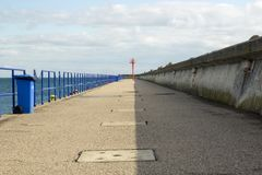 Pilastro concreto sul mare con il faro all'estremità fotografia stock