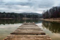 Pilastro del lago alla sera con le colline su fondo Riflessione della foresta nell'acqua verde con il cielo nuvoloso blu Stagno a Fotografie Stock