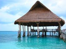 Pilastro della spiaggia con la capanna di Palapa sull'oceano Fotografia Stock