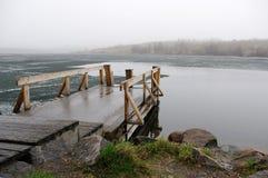 Pilastro di legno al puntello nebbioso del lago Immagini Stock