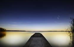 Pilastro di legno che allunga fuori nel lago variopinto Immagine Stock