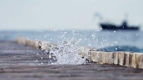 Pilastro di legno che conduce nel mare blu e nella cascata dello spr del mare Fotografie Stock