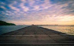 Pilastro di legno del ponte con il bei cielo e nuvole di alba fotografie stock