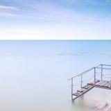 Pilastro di legno della scaletta all'acqua di mare. Esposizione lunga. Immagini Stock