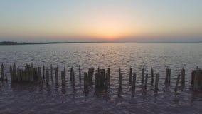Pilastro di legno distrutto abbandonato sul lago ad alba stock footage
