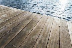 Pilastro di legno e wate increspato blu immagine stock