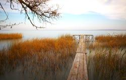 Pilastro di legno sul lago Fotografie Stock
