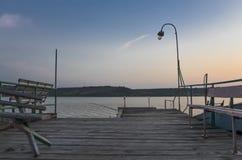 Pilastro di legno sul lago Fotografia Stock