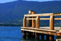 Pilastro di legno sul lago blu Immagine Stock