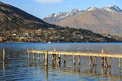 Pilastro di legno sul lago con le montagne nevose del fondo Fotografie Stock