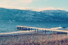 Pilastro di legno sul lago nella stagione invernale fotografia stock
