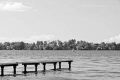 Pilastro di legno sul lago su mancanza e su bianco di giorno di estate Fotografia Stock Libera da Diritti