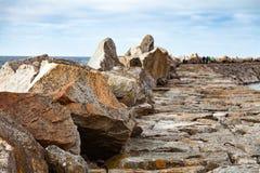 Pilastro di pietra con la gente che cammina su  Fotografia Stock