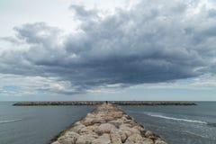 Pilastro di pietra di frangiflutti a Camargue con le nuvole drammatiche sopra il mare Fotografie Stock