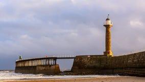 Pilastro e luce ad ovest di Whitby dalla spiaggia a bassa marea Immagine Stock