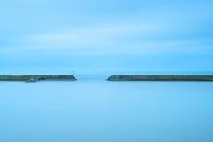 Pilastro e scale concreti in un oceano nuvoloso e blu Fotografia Stock