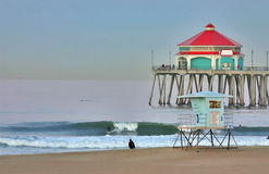 Pilastro e surfista della Huntington Beach all'alba Immagine Stock