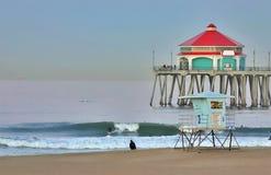 Pilastro e surfista della Huntington Beach all'alba Immagine Stock