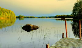 Pilastro nel lago dopo il tramonto fotografia stock